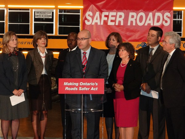 Minister of Transportation Steven Del Duca announces new safety road legislation surrounded by various road safety partners