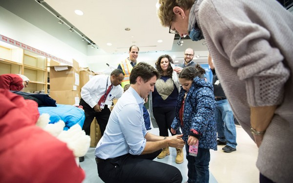 Prime Minister Trudeau is joined by Ontario Premier Kathleen Wynne as they hand out parts of a welcome package to newly arrived Syrian refugees on December 11, 2015.