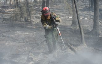 A member of Wildfire Management Alberta's Wild Mountain Unit hoses down hotspots in the Parsons Creek area of Fort McMurray. (Photo: Flickr – Premier of Alberta)
