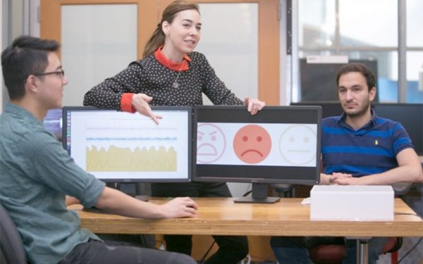 Professor Dina Katabi (center) explains how PhD student Fadel Adib's (right) face is neutral but that EQ-Radio's analysis of his heartbeat and breathing show that he is sad. (Photo: Jason Dorfman/MIT CSAIL)